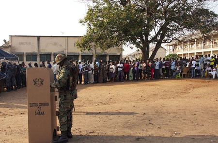File image - A Ghanaian soldier casts his ballot at a polling station as other voters wait in line.