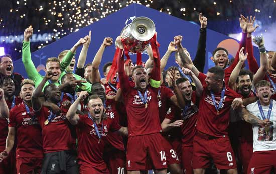 Liverpool's Jordan Henderson lifts the trophy to celebrate with his teammates winning the Champions League final soccer match between Tottenham Hotspur and Liverpool at the Wanda Metropolitano Stadium in Madrid, Saturday, June 1, 2019. (AP Photo/Francisco Seco)
