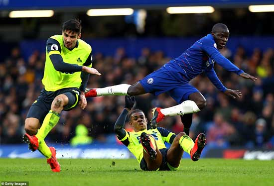 Chelsea's Kante takes a rough tackle from Huddersfield Town's Christopher Schindler and Juninho Bacuna in his side's 5-0 victory on Saturday.