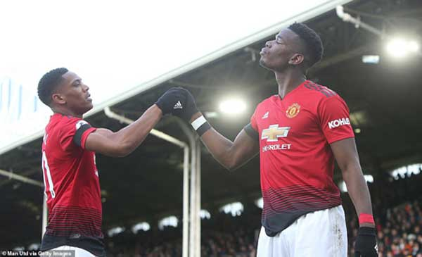 The buoyant midfielder celebrates his strike with France compatriot Martial in front of the away fans.