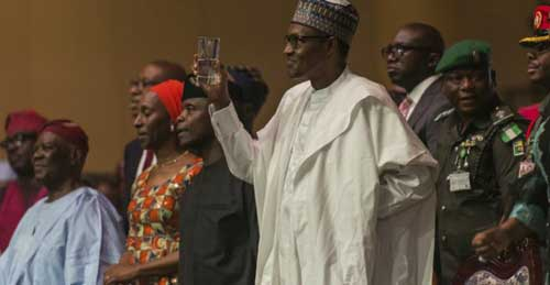 © Stefan Huenis / AFP | Nigerian president Muhammadu Buhari (C) proposes a toast in Lagos, on March 29, 2018.