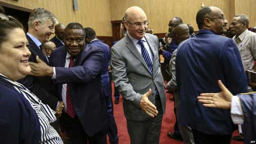 FILE - Jean-Pierre Lacroix, second left, U.N. undersecretary-general for peacekeeping, and Smail Chergui, center, AU commissioner for peace and security, greet delegates after initial peace talks between Central African Republic and armed groups in Khartoum, Sudan, Jan. 24, 2019.