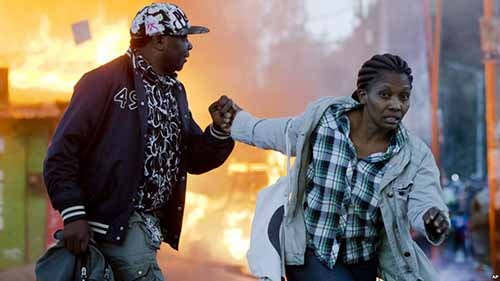 A couple run past burning shops during clashes in Nairobi, Kenya, Oct. 27, 2017.