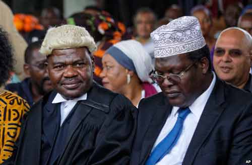 "FILE - Lawyers Miguna Miguna, right, and Tom ""T.J."" Kajwang attend a mock ""swearing-in"" ceremony for opposition leader Raila Odinga at Uhuru Park in downtown Nairobi, Kenya, Jan. 30, 2018."