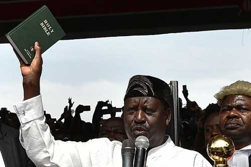 Kenya's opposition leader Raila Odinga (L) holds up a bible during his swearing in ceremony as the People's President of Kenya at Uhuru Park on January 30th, 2018.