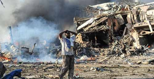 A Somali man reacts next to a dead body on the site where a car bomb exploded at the center of Mogadishu, on October 14, 2017. Photo credit - france24