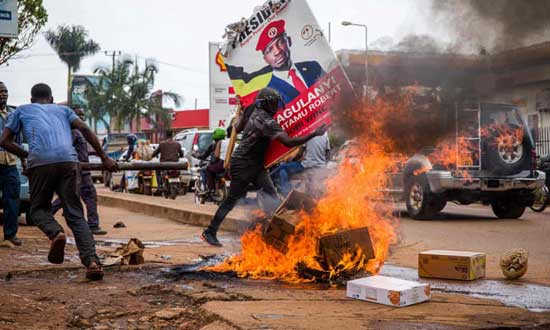A supporter of Ugandan musician turned politician Robert Kyagulanyi, also known as Bobi Wine, carries his poster as protests continue over his arrest. Photograph: Badru Katumba/AFP/Getty Images