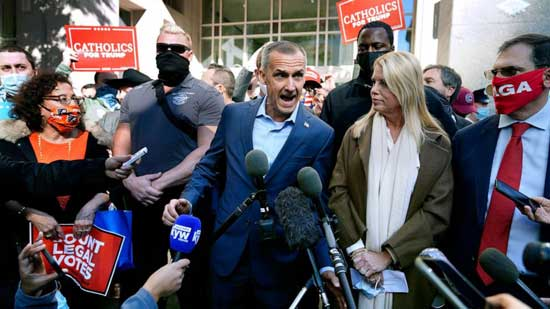 President Donald Trump's campaign advisor Corey Lewandowski, center, speaks about a court order obtained to grant more access to vote counting operations at the Pennsylvania Convention Center, Nov. 5, 2020, in Philadelphia. At right is former Florida Attorney General Pam Bondi.