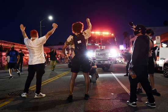 Demonstrators block the path of a Los Angeles Fire Department truck during a public disturbance on Melrose Avenue, Saturday, May 30, 2020, in Los Angeles. Protests were held in U.S. cities over the death of George Floyd, a black man who died after being restrained by Minneapolis police officers on May 25. (AP Photo/Chris Pizzello)