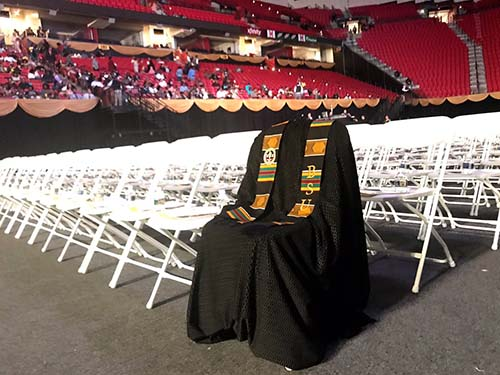 Richard Collins III Honored At Commencement With Graduation Gown On Empty Chair