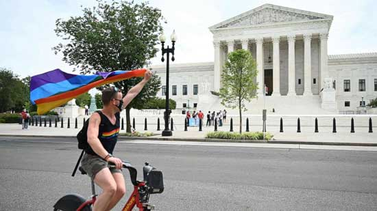A man waves a rainbow flag as he rides by the US Supreme Court that released a decision that says federal law protects LGBTQ workers from discrimination, June 15, 2020, in Washington,DC.A man waves a rainbow flag as he rides by the US Supreme Court that released a decision that says federal law protects LGBTQ workers from discrimination, June 15, 2020, in Washington,DC. Jim Watson/AFP via Getty Images