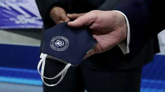 President Donald Trump holds a protective face mask with a presidential seal on it that he said he had been wearing earlier in his tour at the Ford Rawsonville Components Plant in Ypsilanti, Mich., May 21, 2020.President Donald Trump holds a protective face mask with a presidential seal on it that he said he had been wearing earlier in his tour at the Ford Rawsonville Components Plant in Ypsilanti, Mich., May 21, 2020. Leah Millis/Reuters, FILE