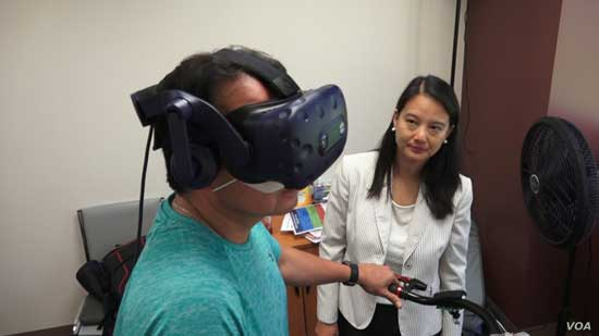 Keck School of Medicine of USC assistant professor Judy Pa watches as Wayne Garcia participates in a study that looks at whether virtual reality combined with exercise can prevent dementia. (E. Lee/VOA)