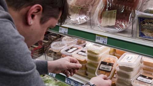 "A worker removes expired food in a local supermarket in Brussels on Jan. 16, 2017. The European Court of Auditors chided the European Union's executive branch in a report, ""Combating Food Waste,"" that decries the bloc's lack of effort in reducing the food waste, estimating the EU wastes 88 million tons of food per year."