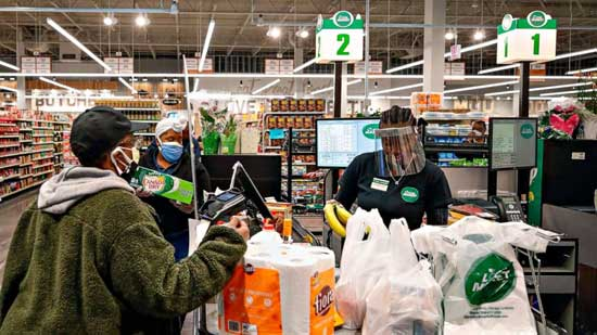 A cashier wearing a face shield bags groceries for a customer at the Local Market Foods store in Chicago, April, 8, 2020. AFP photo
