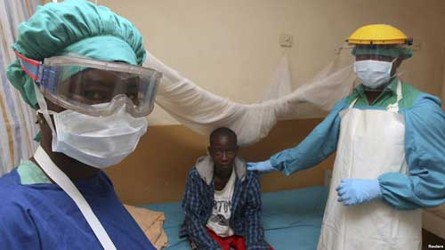 FILE - A Sierra Leonean nurse and doctor stand by a patient in a Lassa fever ward at Kenema Government Hospital in southeastern Sierra Leone, Feb. 7, 2011.