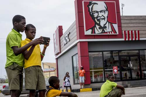 Ghanaian shool kids wait for breakfast outside a KFC eatery.