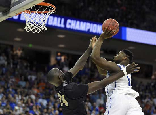 Duke's Zion Williamson, right, shoots over Central Florida's Tacko Fall during the second half of a second-round men's college basketball game in the NCAA Tournament in Columbia, S.C., Sunday, March 24, 2019. (AP Photo/Richard Shiro)