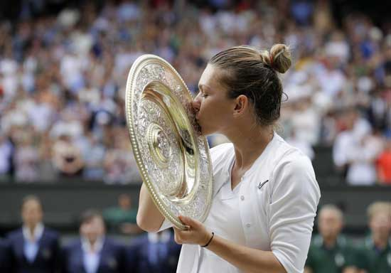Romania's Simona Halep kisses the trophy after defeating United States' Serena Williams during the women's singles final match on day twelve of the Wimbledon Tennis Championships in London, Saturday, July 13, 2019. (AP Photo/Kirsty Wigglesworth)