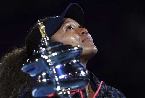 Japan's Naomi Osaka holds the Daphne Akhurst Memorial Cup aloft defeating United States Jennifer Brady in the women's singles final at the Australian Open tennis championship in Melbourne, Australia, Saturday, Feb. 20, 2021.(AP Photo/Mark Dadswell)