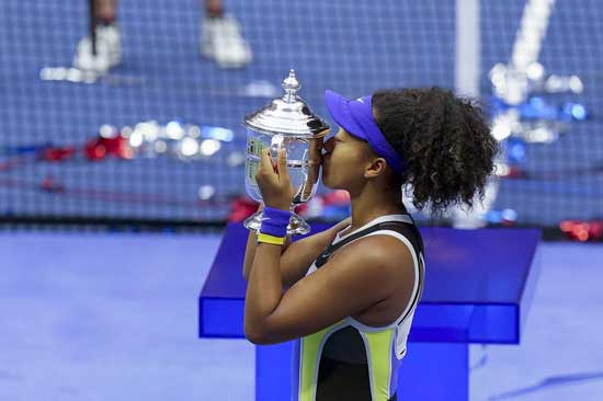 Naomi Osaka, of Japan, holds up the championship trophy after defeating Victoria Azarenka, of Belarus, in the women's singles final of the US Open tennis championships, Saturday, Sept. 12, 2020, in New York. (AP Photo/Seth Wenig)