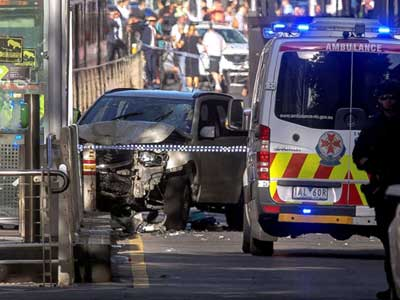 Australian police stand near a crashed vehicle after they arrested the driver of a vehicle that had rammed into pedestrians at a crowded intersection near the Flinders Street train station in central Melbourne, Australia, Dec. 21, 2017.