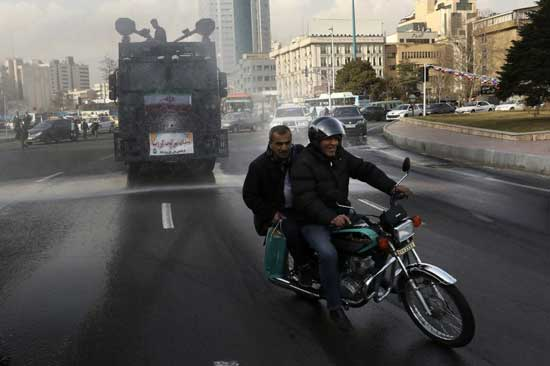 In this Sunday, March 1, 2020 photo, a police vehicle disinfects streets against the coronavirus, in Tehran, Iran. AP photo