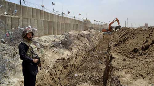 FILE - In this May, 16, 2014 file photo, a Pakistani border guard stands alert as an excavator digs a trench along Pakistan Afghanistan border at Chaman post in Pakistan.