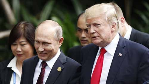U.S. President Donald Trump, right, and Russia's President Vladimir Putin, center, talk during a group photo session at the APEC Summit in Danang, Vietnam, Nov. 11, 2017. VOA photo