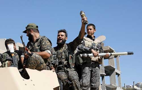 Fighters of Syrian Democratic Forces celebrate after Raqqa in Syria was liberated from Islamic State militants. PBS photo.