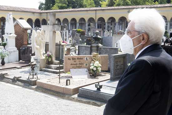 FILE - In this Tuesday, June 2, 2020 file photo, Italian President Sergio Mattarella stands silent in front of graves, at the cemetery of Codogno, Italy, where the first case of COVID-19 emerged.