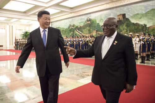 China's President Xi Jinping, left, and Ghana's President Nana Akufo-Addo, right, review the honor guard of Chinese People's Liberation Army during the welcome ceremony at the Great Hall of the People Saturday, Sept. 1, 2018. (Nicolas Asfouri/Pool Photo via AP)