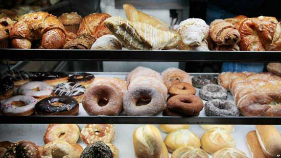 A selection of donuts, bagels, rolls, croissants, turnovers and sticky buns are displayed in a New York coffee cart, April 10, 2012. File image