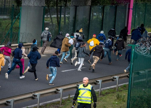 Migrants trying to reach the Channel Tunnel run past a policeman on the Eurotunnel site in Coquelles near Calais, northern France, on July 29, 2015.