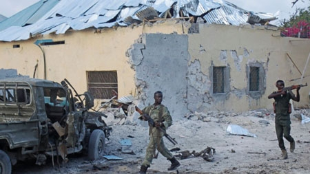 Somali soldiers take position after a bomb that was detonated at the gate of one of Mogadishu's most popular hotel. Friday, March, 27, 2015, A Somali police official says a suicide bomber has detonated his explosives-laden car at the gate of a hotel popular with government officials in Mogadishu. Capt. Mohamed Hussein says gunfire could be heard inside the Maka-Mukarramah Hotel, but it was not clear if any gunmen had managed to penetrate the hotel's gate.
