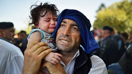 A man holds his crying child close to him as migrants force their way through police lines at Tovarnik station for a train to take them to Zagreb, Croatia