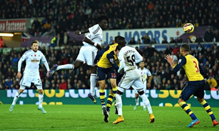Bafetimbi Gomis, centre, rises to head Swansea City's winner against Arsenal. Photograph