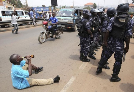 A supporter of opposition leader Kizza Besigye drinks beer in front of riot policemen in Kampala, Uganda.