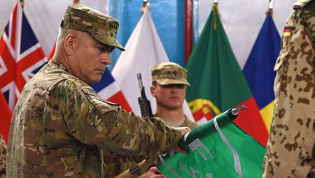 General John Campbell (L) rolls the flag of the NATO-led International Security Assistance Force (ISAF) during a ceremony marking the end of ISAF's combat mission in Afghanistan at ISAF headquarters in Kabul on December 28, 2014.