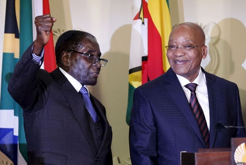 Library photo -  Zimbabwe's President Robert Mugabe (L) gestures as South Africa's President Jacob Zuma looks on at the end of a press briefing at the Union building in Pretoria, April 8, 2015.