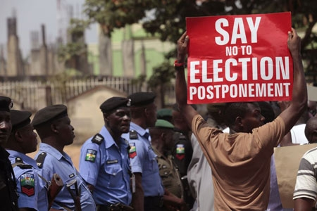 A protestor holds a banner as Nigerian security forces look on, during a protest in Abuja, Nigeria, Saturday, Feb. 7, 2015, against the possible postponement of the Nigerian elections. Civil rights groups staged a small protest Saturday against any proposed postponement.
