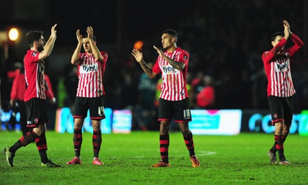 Exeter City's Jamie Reid applauds the fans with his teammates at the end of the match.
