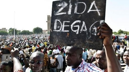 "A man holds up a placard that reads in French, ""Zida get out"", referring to Isaac Zida"