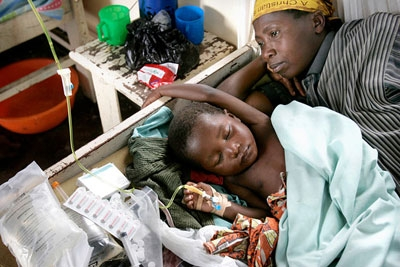 A father lies behind a child recovering from Malaria in a hospital