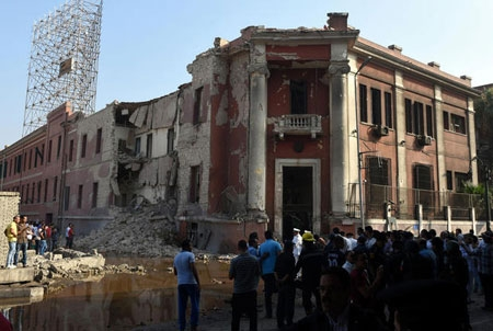 Egyptian security and citizens look at the the destroyed facade of the Italian consulate building following a powerful bomb explosion, killing one person, in the capital, Cairo