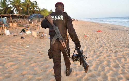 An Ivorian soldier patrols the beach after the attack