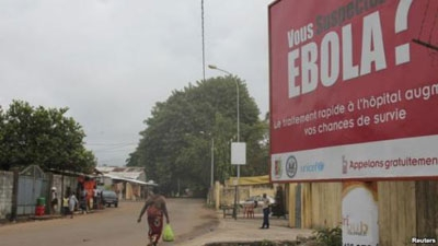 A public service advisory billboard with a message about Ebola appears on a street in Conakry, Guinea.