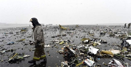 An emergency worker walks through wreckage of the FlyDubai passenger jet that tried to land in bad weather in the city of Rostov-on-Don.